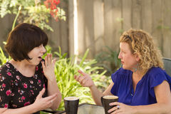 Two women sharing and chatting over coffee. Women and friendship sharing stories over a cup of coffee outdoors Stock Images