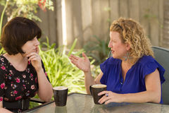 Two women sharing and chatting over coffee. Royalty Free Stock Image