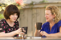 Two women sharing and chatting over coffee. Women and friendship sharing stories over a cup of coffee outdoors Royalty Free Stock Image