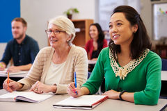 Two women sharing a desk at an adult education class look up