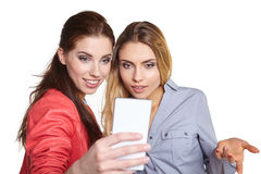 Two women sharing social media in a smart phone Royalty Free Stock Photography
