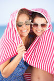 Two Women Sheltering From Sun On Beach Holiday. Under Beach Towel Stock Image