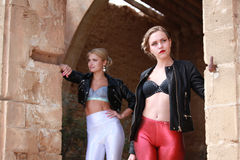 Two women in shiny leggings and leather jackets Stock Photos