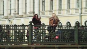 Two women are shooting photos on the bridge stock video