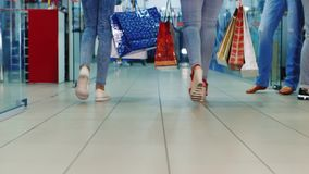Two women with shopping bags are on the shopping center. Rear view, only legs visible. HD video stock footage