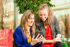 Two women shopping with bags in mall. Two female friends having fun while shopping in a mall, they bought a e-book stock photo