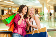 Two women shopping with bags in mall. Two female friends with shopping bags having fun while shopping in a mall stock photography