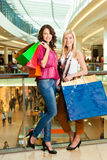 Two women shopping with bags in mall Royalty Free Stock Photo