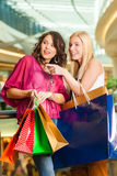 Two women shopping with bags in mall. Two female friends with shopping bags having fun while shopping in a mall royalty free stock image