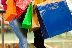 Two women shopping with bags in mall. Two female friends with shopping bags having fun while shopping in a mall, close-up on bags stock photo