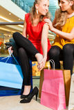 Two women shopping with bags in mall. Two female friends with shopping bags having fun while shopping in a mall, close-up on bags stock image