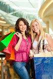 Two women shopping with bags in mall. Two female friends with shopping bags having fun while shopping in a mall Stock Images