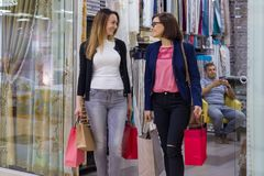 Two women with shopping bags in mall. Background shop for home decor and interior fabrics. Two women with shopping bags in mall. Background shop for home decor Stock Photos
