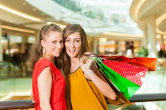 Two women shopping with bags in mall. Two female friends with shopping bags having fun while shopping in a mall Stock Photo