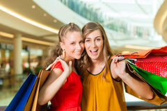 Two women shopping with bags in mall. Two female friends with shopping bags having fun while shopping in a mall stock image