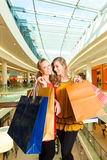 Two women shopping with bags in mall. Two female friends with shopping bags having fun while shopping in a mall royalty free stock photo