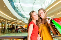 Two women shopping with bags in mall. Two female friends with shopping bags having fun while shopping in a mall royalty free stock photography