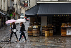 Two women with shopping bags ounder umbrellas Royalty Free Stock Photos