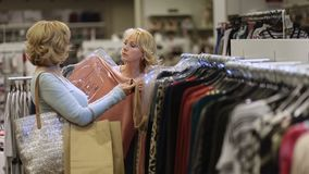 Two women shopping clothes in fashion department stock footage
