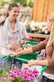 Two women shopping in garden center talking Royalty Free Stock Images