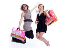 Two women shopping and jumping in a white backgrou. Shopper: women with shopping bags in a white background Stock Image