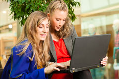 Two women shopping in mall with laptop. Two female friends having fun while shopping in a mall, they bought a e-book stock images