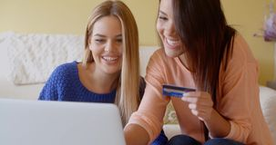Two women shopping online with computer stock footage