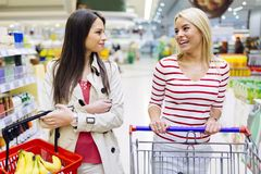 Two women shopping in supermarket Stock Images