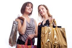 Two women shopping in a white background. Royalty Free Stock Image