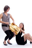 Two women shopping in a white background. Shopper: Two women fighting for a shopping bag in a white background Royalty Free Stock Photography