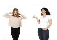 Two women shot with one woman laughing and making fun and other women is in shock and offended. Lifestyle photo on white backgroun Stock Images