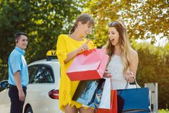 Two women showing each other their shopping in bags. Getting out of taxi stock images