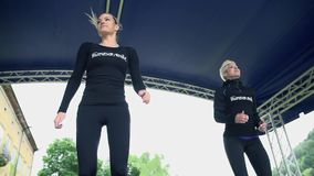 Two women showing exercises on stage stock footage