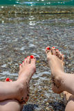 Two women showing their feet with red painted nails over the ocean background Royalty Free Stock Images