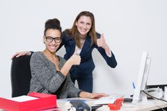 Two women are showing their thumbs up. Two business women are holding their thumbs up at the desk in the office while smiling to the camera Royalty Free Stock Photos