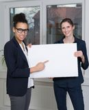 Two women are showing a whiteboard Stock Photos