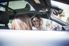 Two women singing in the car. Young and beautiful women singing and dancing to the rhythm of music in their car stock images
