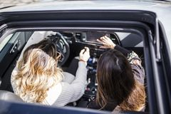 Two women singing in the car. Young and beautiful women singing and dancing to the rhythm of music in their car, aerial view royalty free stock images