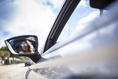 Two women singing in the car. Young and beautiful women singing and dancing to the rhythm of music in their car, one women looking back through the mirror stock image