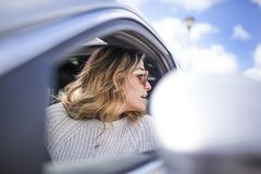 Two women singing in the car. Young and beautiful woman singing and dancing to the rhythm of music in their car, one woman looking back through the window stock image