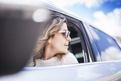 Two women singing in the car. Young and beautiful woman singing and dancing to the rhythm of music in their car, one woman looking back through the window royalty free stock images