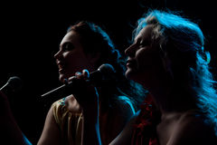 Two women singing in microphone Royalty Free Stock Images