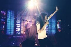 Two women singing in the night club. Two women having fun together in the night club while singing under a disco ball with bright rays Stock Images
