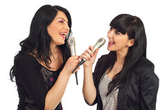Two women singing to microphones. Two happy women singing to microphones and having fun isolated on white background royalty free stock images