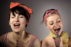 Two women singing together. Karaoke, retro style royalty free stock photography