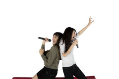 Two women singing together in the studio. Two women having fun together while singing karaoke, isolated on white background Royalty Free Stock Photography