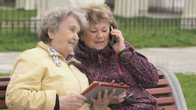 Two women sit and discuss about nature outdoors. One woman aged 80s dressed in yellow jacket holds computer tablet another woman talking with friend using a stock footage