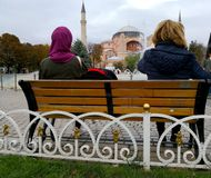 Two women sit in front of the fountain of Sultan ahmet Square and look at the Hagia Sophia stock photography