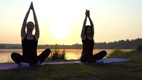 Two Women Sit on Mats, Raise Arms Up, Relax at a Yoga Pose at Sunset in Slo-Mo. Two Sportive Women Sit on Mats in a Semi-Lotus Pose, Raise Their Arms Up, Relax stock video footage