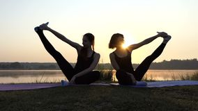 Two Women Sit on Mats, Raise Legs Aside, Smile, at a Splendid Sunset. Two Young Women Sit on Mats Near Each Other, Touch One Foot With Their Fingers, Raise One stock video footage